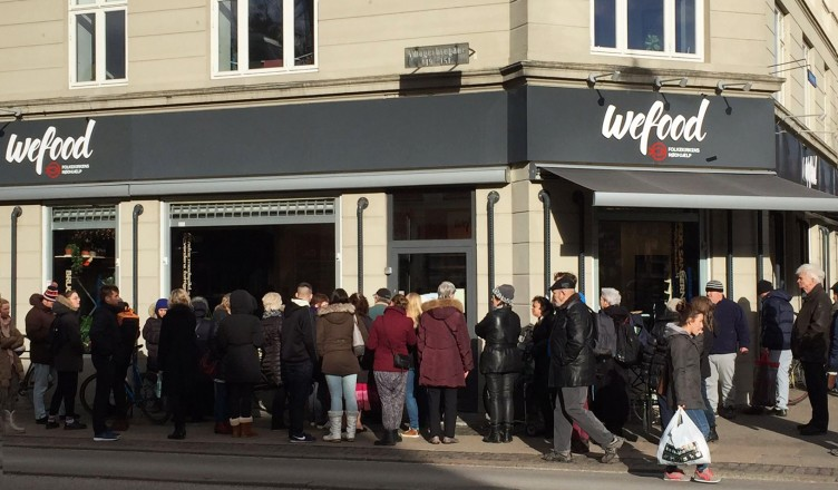 """A crowd waits on the sidewalk for the WeFood grocery store in Copenhagen to open. It's not the first grocer in Europe to sell surplus food. But unlike so-called """"social supermarkets"""" – stores which serve almost exclusively low-income people — WeFood's offerings are very intentionally aimed at the general pub"""